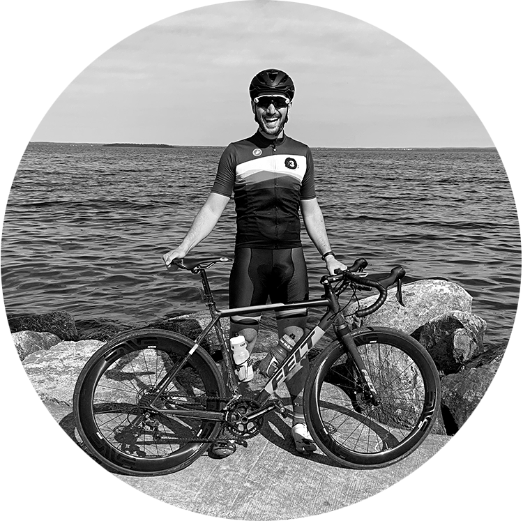 Coach Michael standing with his bike, smiling in front of a lake